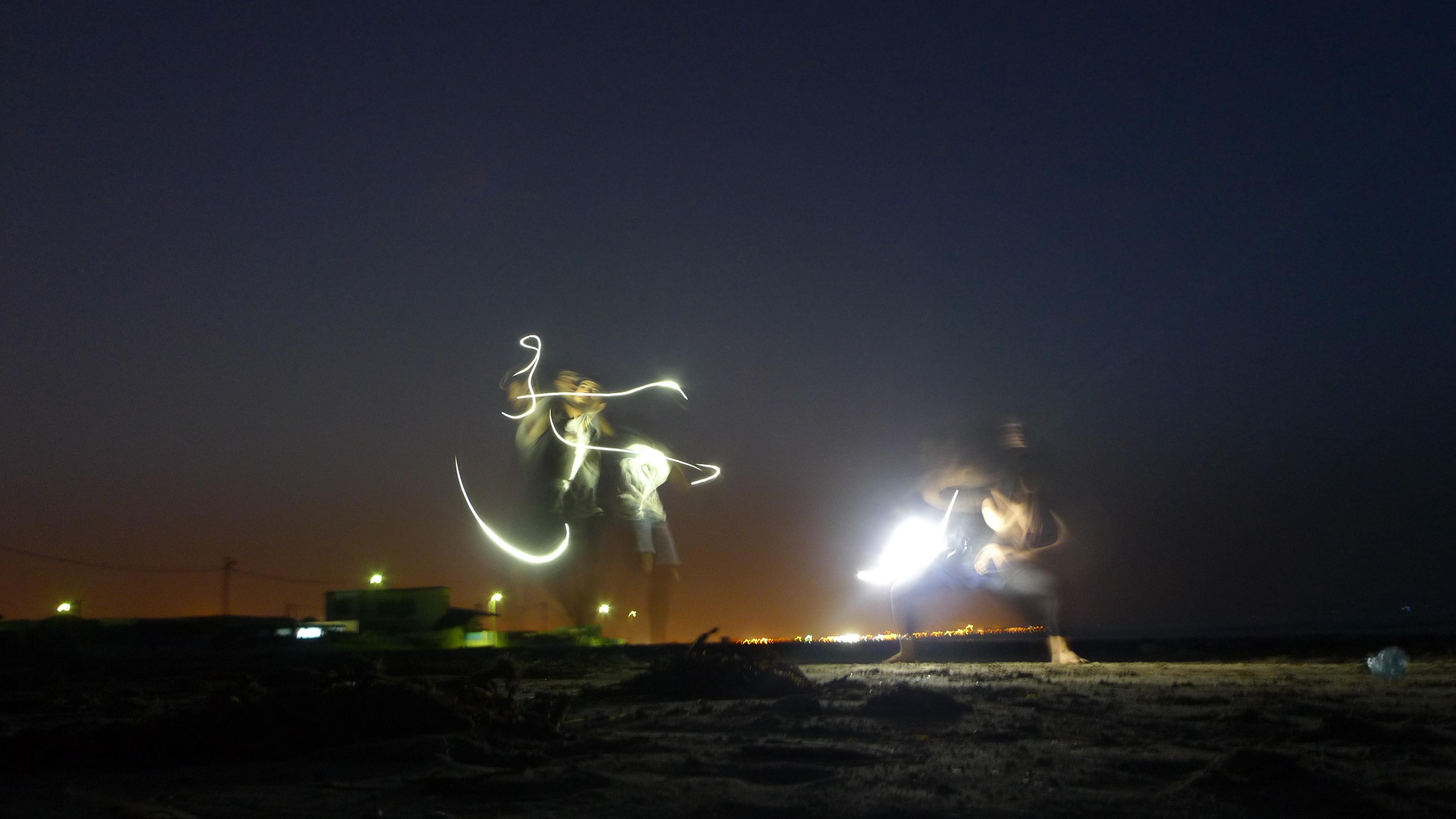 Sur la plage une performance s'improvise dans la nuit, éclairée par la lumière des téléphones portables